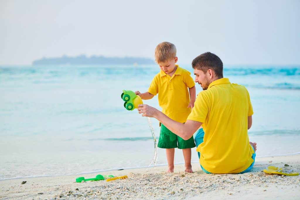 Three year old toddler boy on beach with father. by Krystal International Vacation Club